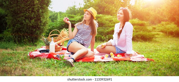Two beautiful young girls at a picnic in the summer in the park eating apples and talking