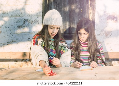 Two beautiful young girls play a board game with dice on a sunny winter day. Countryside background, cross process sunny glow look.