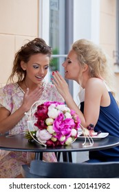 two beautiful young girls in summer outfit gossip at the cafe table with a bunch of flowers and a dessert on it