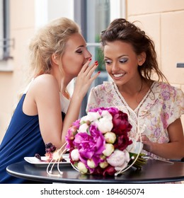 two beautiful young girls in summer dresses gossip at the cafe table with a bunch of flowers and a dessert on it