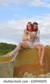 Two beautiful young hippie girls pose outdoors and show each other a feeling of friendship and affection.