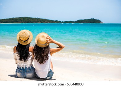 Two beautiful young hipster girls sit on the seashore, the ocean, look at the turquoise water, enjoy the sun, are dressed in white T-shirts, denim shorts, vacation in a tropical country, travel