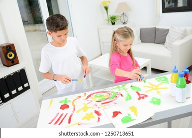 two beautiful young kids boy and girl hand painting on a white paper with color paint