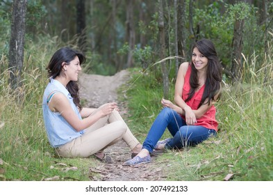 Two beautiful young latin girls sitting in a forest smiling and talking