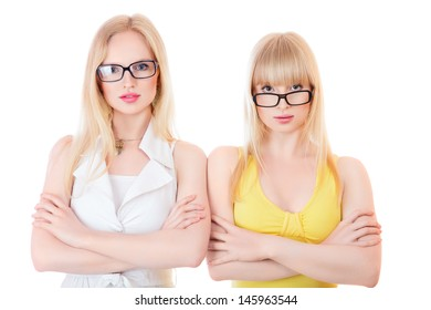 Two beautiful young serious women in glasses isolated on white background
