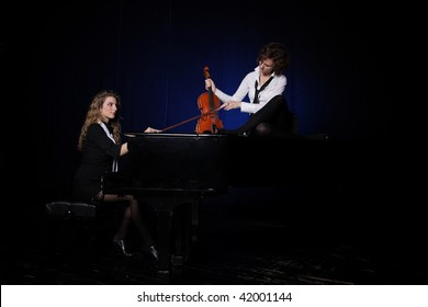 Two beautiful young sexy women posing with violin and piano