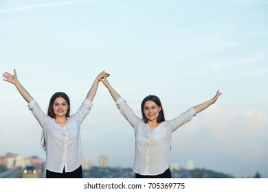 two beautiful young sisters twin girls on blue sky background with smiles