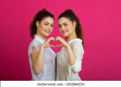 two beautiful young sisters twins in a good mood in white blouses on a pink background showing a hand gesture in the form of a heart