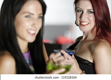 Two beautiful young woman chatting and drinking cocktails at a nightclub or wine bar.