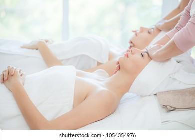 two beautiful young woman enjoying face massage relaxing in beauty spa salon