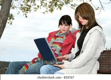 Two beautiful young woman (hispanic and caucasian) sitting outside by the fireplace with laptop.  Wearing winter clothes.