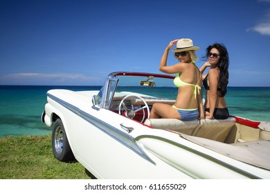 Two beautiful young women brunette and blond in swimsuits sit in retro car cabriolet near caribbean coastline at summer sunny day