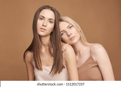 Two beautiful young women with a different skin type dressed in tops of natural color on a brown background, natural makeup, beautiful radiant skin, long shiny hair.