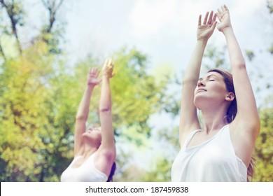 Two beautiful young women doing yoga class in nature.