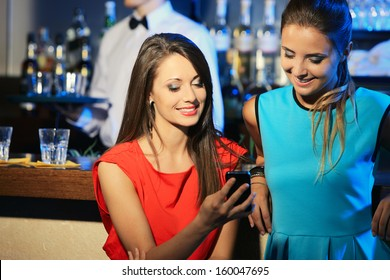 Two beautiful young women friends having fun looking on their smart cell phone