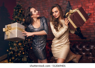 Two beautiful young women give Christmas gifts and dancing in club. Christmas party. Happy New Year 2017.