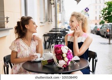 Two beautiful young women with great smile and hairstyle sitting at a bar, drinking tea and coffee.