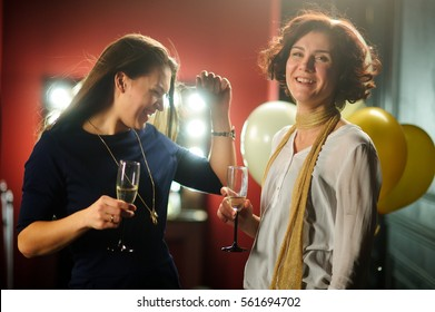 Two beautiful young women have a good time at a party. Girlfriends drink wine and cheerfully communicate.