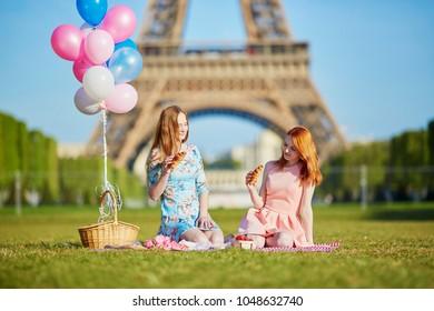 Two beautiful young women having picnic near the eiffel tower in Paris, France
