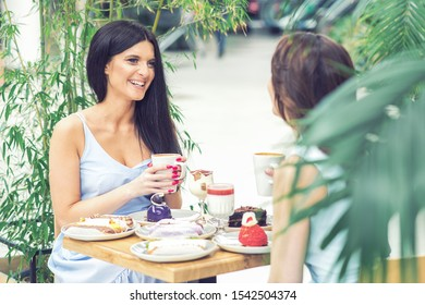Two beautiful young women are having coffee and desserts together on vacation at outdoors cafe. Girls chats while sitting at cafe.