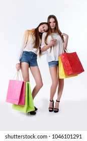 two beautiful young women in high heels, holding a few shopping bags, smiling and looking happy.
