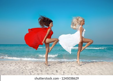 Two Beautiful young women jumping on the beach with a colored sarong. Cheerful girls. Summer leisure vaction. Skin care leg laser epilation.