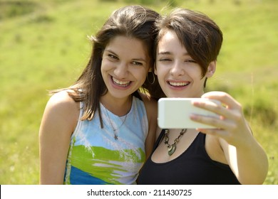 Two beautiful young women laughing and having fun with smart phone
