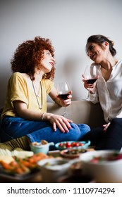 Two beautiful young women, looking at each other, drinking red wine and having a chat (selective focus)