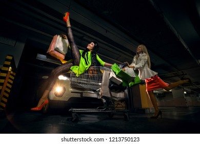 Two beautiful young women in a modern car parking. One of them sitting on metal shopping trolley with a lot of shopping bag
