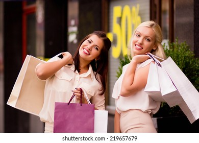 Two beautiful young women with shopping bags smiling, standing outside the shop. Overstock, cheerful shopping