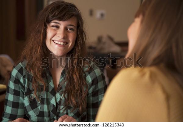 Zwei schöne junge Frauen sitzen zusammen und sprechen.