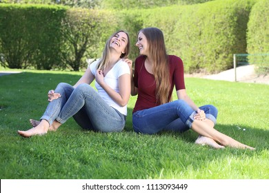 Two beautiful young women sitting bare feet on grass laughing