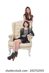 Two beautiful young women sitting in old chair