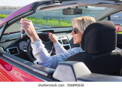 Two beautiful young women sitting in the car and enjoy.Colored and under exposed photo