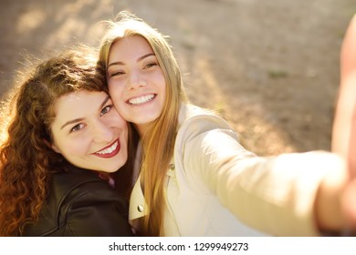 Two beautiful young women take selfie on sunny park. Girlfriends. Communication and gossip.