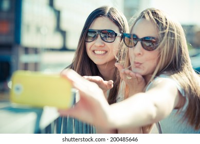 two beautiful young women using smart phone for selfie in the city
