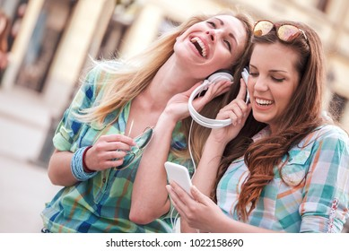 Two beautiful young women walking down the street and listening to music, have fun with mobile phone. Lifestyle, fashion, technology