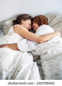 Two beautiful yuong women sleeping on bed together. Lesbian lovers and couple concept. People and lifestyles theme. LGBT pride theme