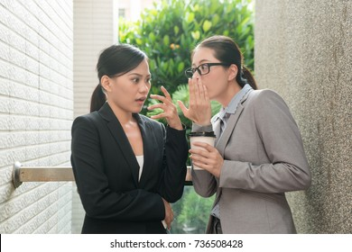 two beauty Asian women conversation about office rumor gossip and feel shocked at rest time outdoor of the company.