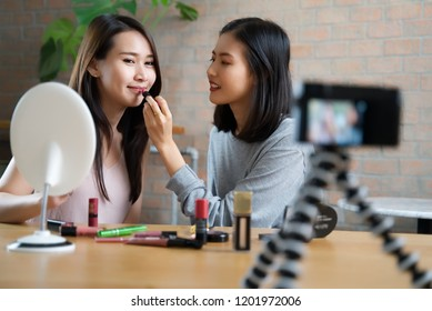 Two beauty blogger Asian cute girls presenting beauty cosmetic products and broadcasting live video to social network. Focus on the blogger girls. Beauty blogger concept.