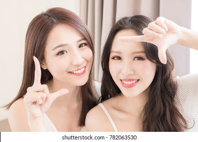 two beauty woman making frame gesture in the home