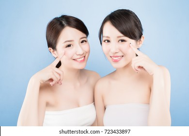 two beauty woman pointing her eye with healthy skin care on the blue background