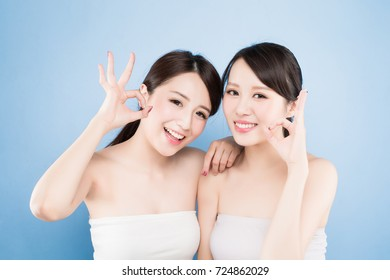 two beauty woman show ok toy you with healthy skin care on the blue background