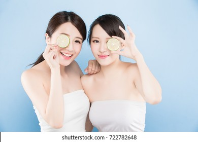 two beauty woman take lemon with make up concept on the blue background