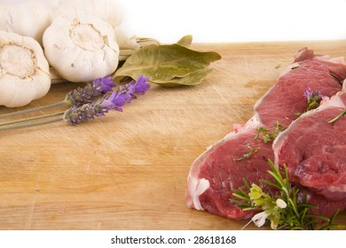 Two beef steaks, and a set of Mediterranean ingredients over a wooden board ready to be chopped and used to flavor a meal
