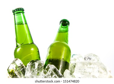 Two beer bottles getting cool in ice cubes