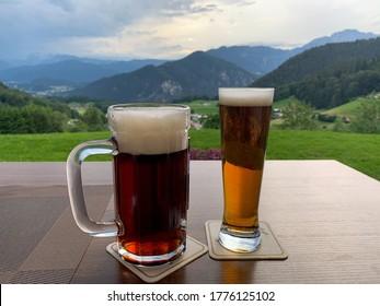 Zwei Biergläser mit dunklem Bayerischen Bier auf dem Holztisch, Nahaufnahme auf unscharfem Hintergrund der alpinen Berglandschaft