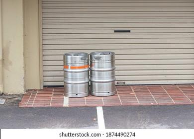 Two beer kegs in front of a roller door