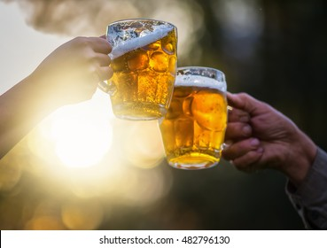 Two beer mugs clink