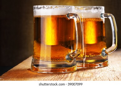 Two beer mugs close-up on wooden table